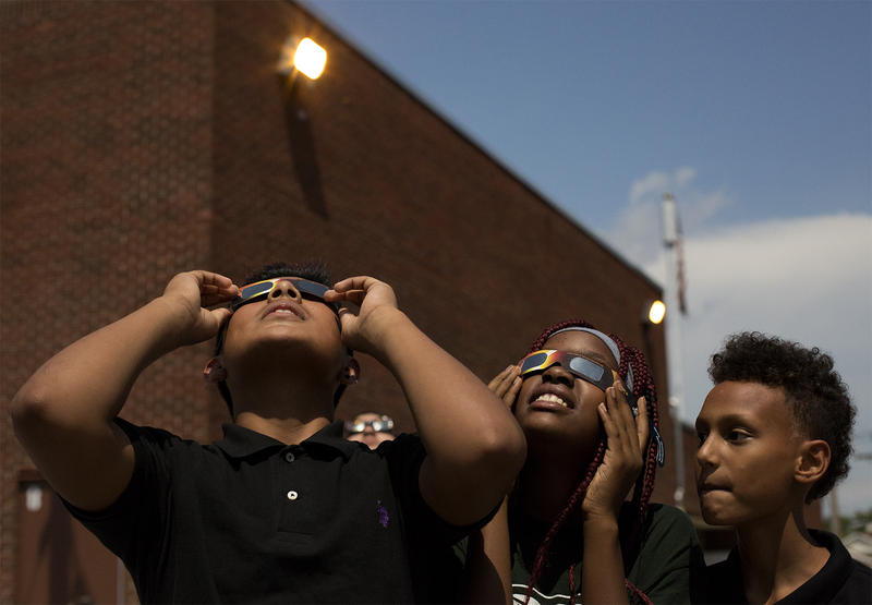 Avian Flores, Racheal Byenga and Malik Davidson look up at the eclipse at Long International Middle School in St. Louis.