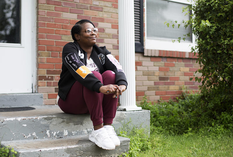 Tracy White sits in front of her mother's house, where she's living after serving more than 18 years in prison.