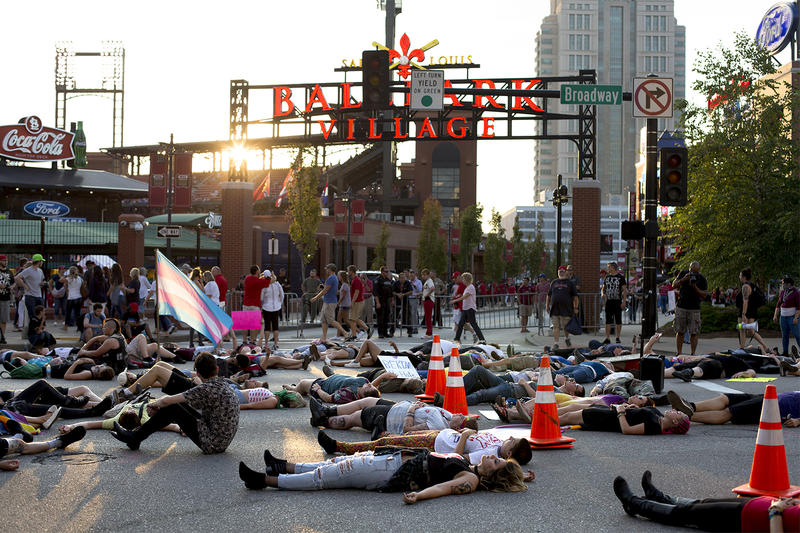 After protesting the presence of Westboro Baptist Church members outside Busch Stadium on Cardinals Pride Night, demonstrators lie in the street in honor of Kiwi Herring, a black trans woman who was killed by St. Louis police this week. Aug. 25, 2017