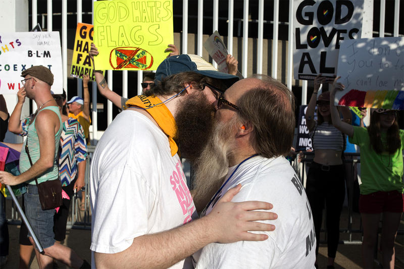 Graham Matthews and Stephen Houldsworth kiss in front of barricades set up around members of the Westboro Baptist Church. Aug. 25, 2017