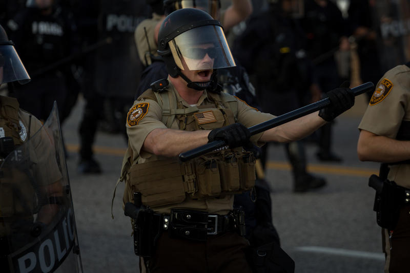 A St. Louis County police officer advances toward protesters blocking Brentwood Blvd. Wednesday evening.