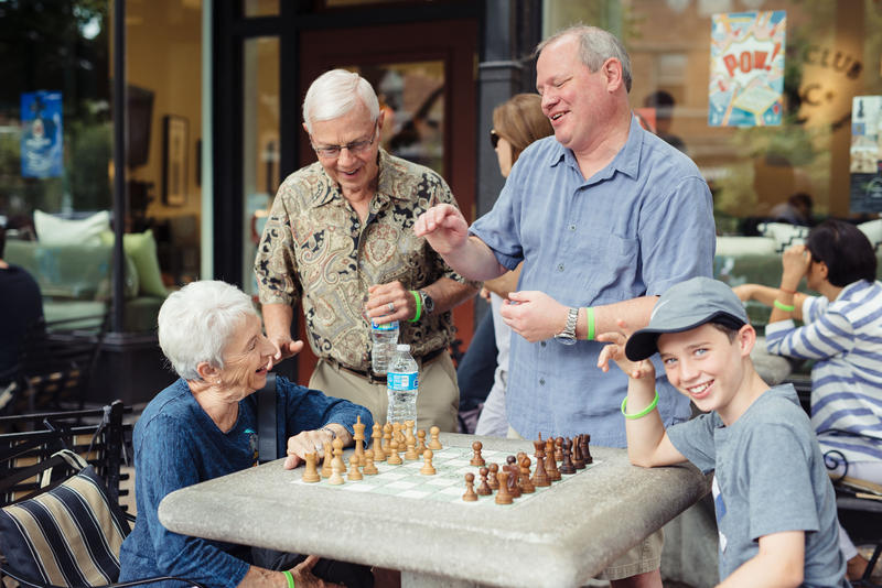People enjoying a game of chess outside the Chess Club