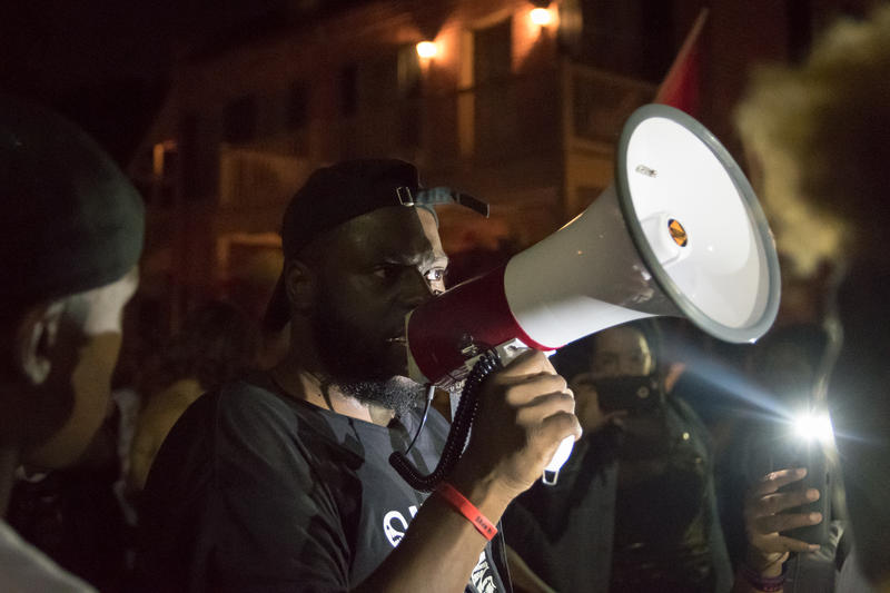 A protester speaks to the crowd during a demonstration in downtown St. Charles Friday night.  It was the eighth day of protests following the not-guilty verdict of white ex-St. Louis police officer Jason Stockley on first-degree murder charges.