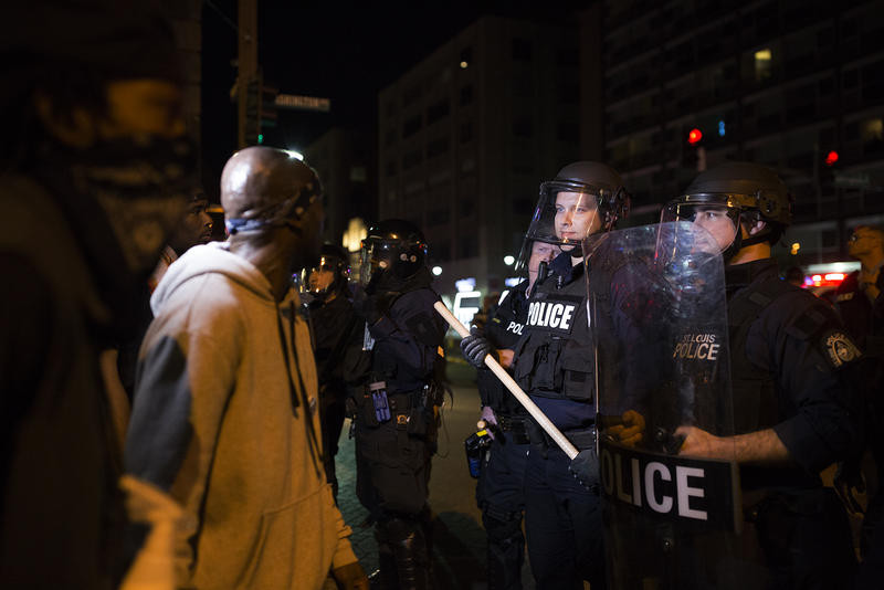 A St. Louis police officer laughs while facing off with emotional protesters on Washington Ave. in downtown St. Louis.