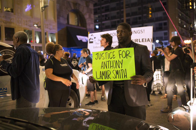 Bishop Derrick Robinson holds a sign in front of an unmarked police car on Washington Ave. in downtown St. Louis. Sept. 28, 2017