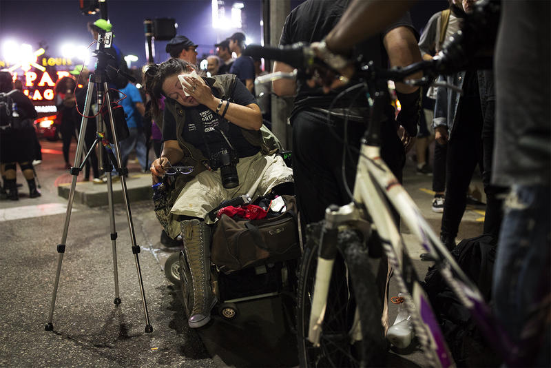 Livestreamer Heather De Mian wipes her eyes after police sprayed chemicals at demonstrators near Busch Stadium.