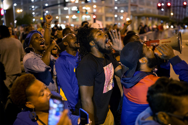 Protesters, including Marcellus Buckley, center, chant outside Busch Stadium during a Cardinals game. Sept. 29, 2017