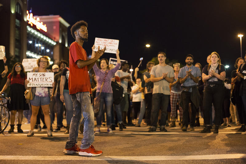 Rasheen Aldridge, activist and democratic committeeman for the 5th Ward, leads protesters in a chant outside Busch Stadium. Sept. 29, 2017
