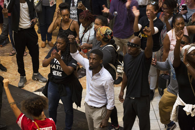 Demonstrators stand where police arrested several protesters a week earlier at the St. Louis Galleria.