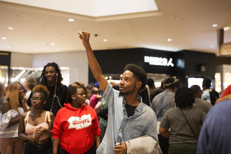 Rasheen Aldridge watches as shoppers descend an escaltor to join the protest.