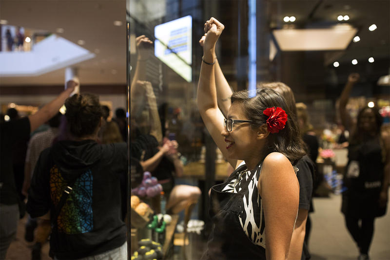 Workers watch protesters from inside a store at the St. Louis Galleria. Sept. 30, 2017
