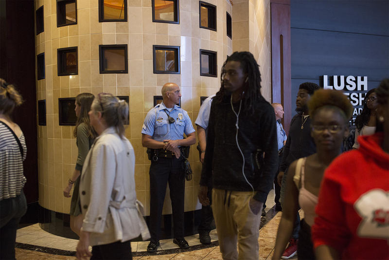 Police officers stand by as protesters march through the St. Louis Galleria. Sept. 30, 2017