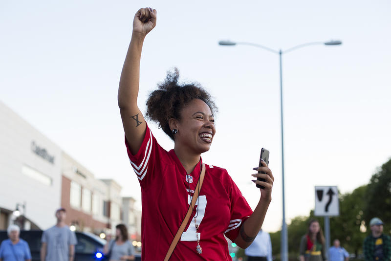 LaShell Eikerenkoetter raises a fist while livestreaming the protest at the St. Louis Galleria. Sept. 30, 2017