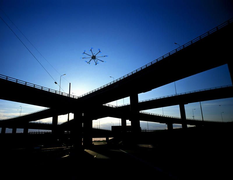 A drone flies near a bridge