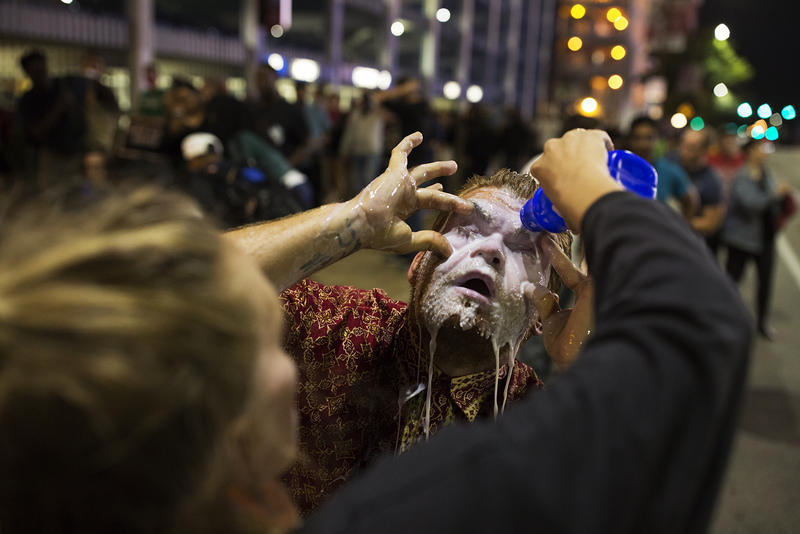 A street medic assists a protester after St. Louis police officers sprayed checmicals into a crowd of demonstrators near Busch Stadium on Sept. 29, 2017.