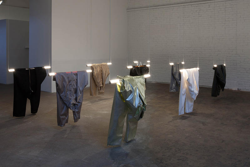 Several suits made of different fabric types, including plastic and cloth, hang over individual florescent lights.