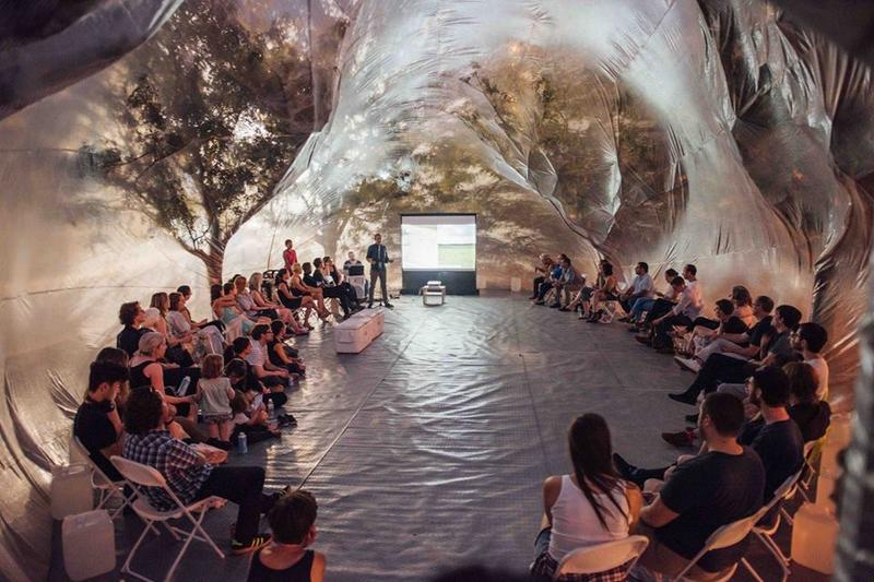 People gather inside a giant inflatable bubble to listen to presentations about art