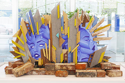 Two blue faces framed by jagged wood pieces rest on a bed of brick laid across a pedistal.
