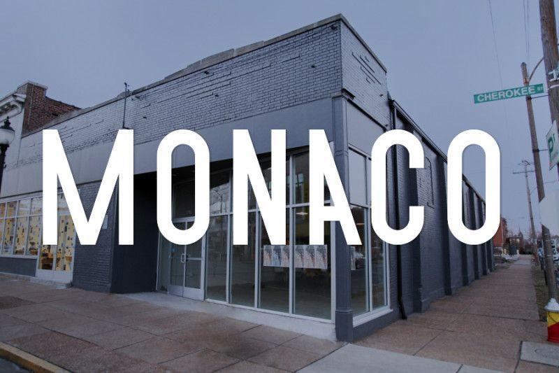 The word Monaco is laid out across a photo of a large 1-story brick and glass building.