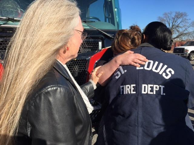 The widow of firefighter Marnell Griffin (her back to the camera) comforts a fellow firefighter's widow on Dec. 201, 2017. They, and the woman on the left, lost their husbands to cancer.