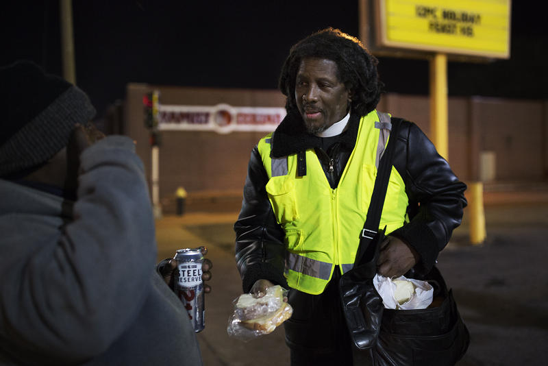 The Rev. Ken McKoy hands sandwiches and snacks on North Kingshighway Blvd. on a cold night.