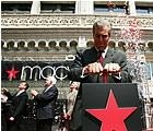 Terry Lundgren, Chairman, President and CEO of Federated Department Stores, Inc. pushes down on a plunger, releasing confetti into the streets of St. Louis to mark the beginning of the Macy's era on Friday.   (UPI Photo/Bill Greenblatt)
