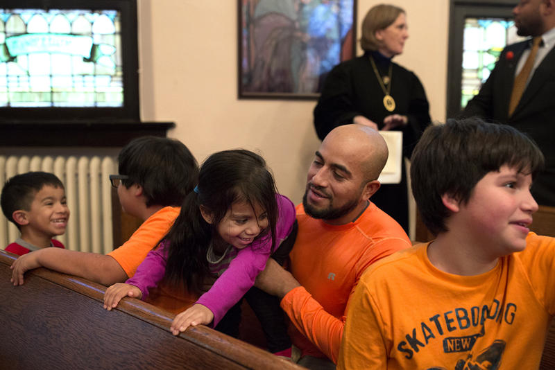 Alex Garcia jokes with his 3-year-old daughter, AriannaLee, while sitting with kids before the start of a church service.