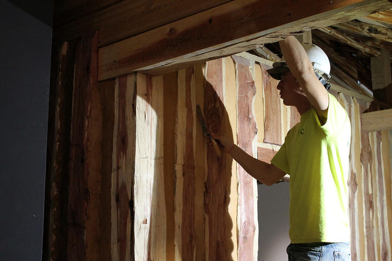 A construction worker puts finishing touches on a French Creole cabin in the redesigned museum beneath the Gateway Arch.