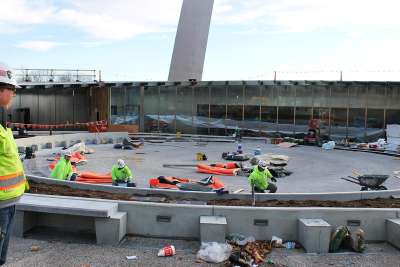 Construction workers are installing a water fountain that will greet visitors to the renovated Gateway Arch grounds prior to walking into the visitor center.