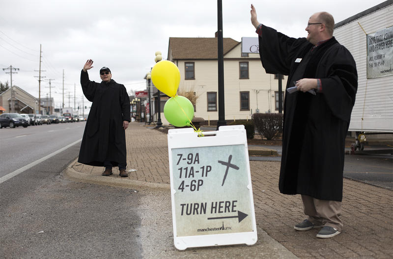 Pastor Phil Estes, left, encourages motorists to get ashes at
