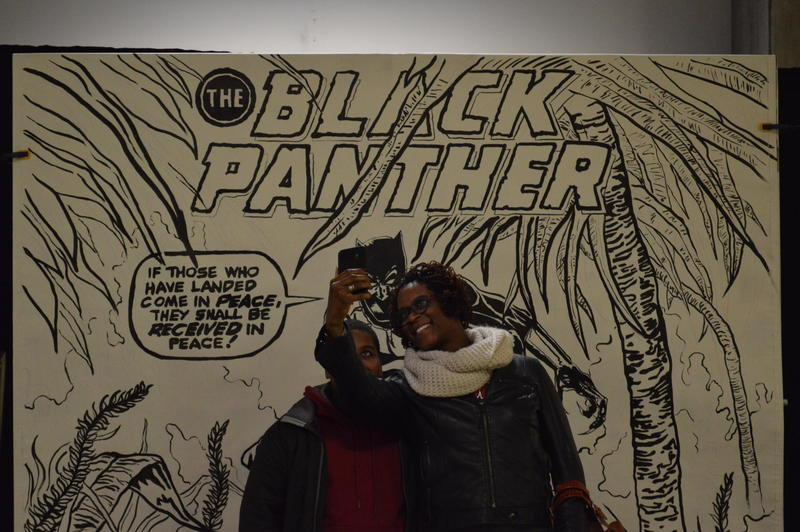Families take photos next to a Black Panther banner at the St. Louis Science Center First Friday event dedicated to Black Panther on Feb. 2., 2018
