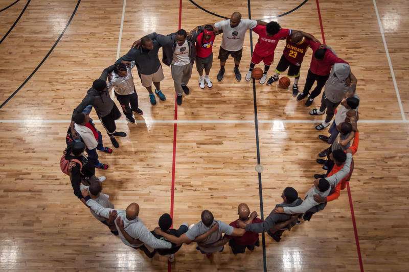 Basketball players huddle for a prayer at the Monsanto Family YMCA.