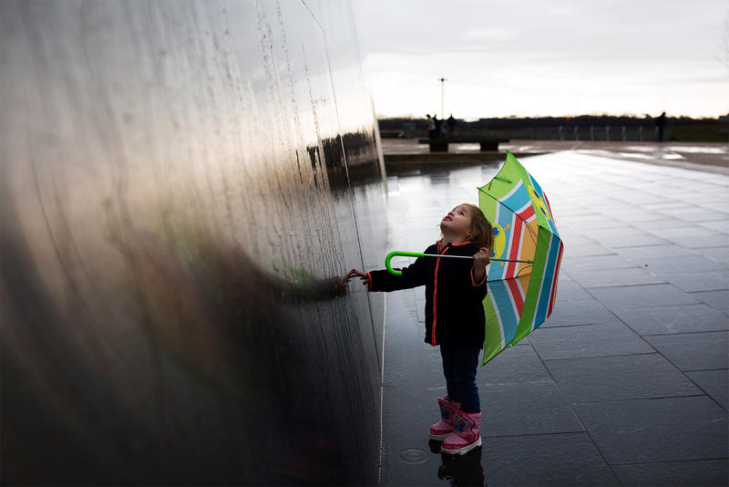 Three-year-old Brigid Horn looks up at the Gateway Arch after the opening of the Park Over the Highway. March 26, 2018.