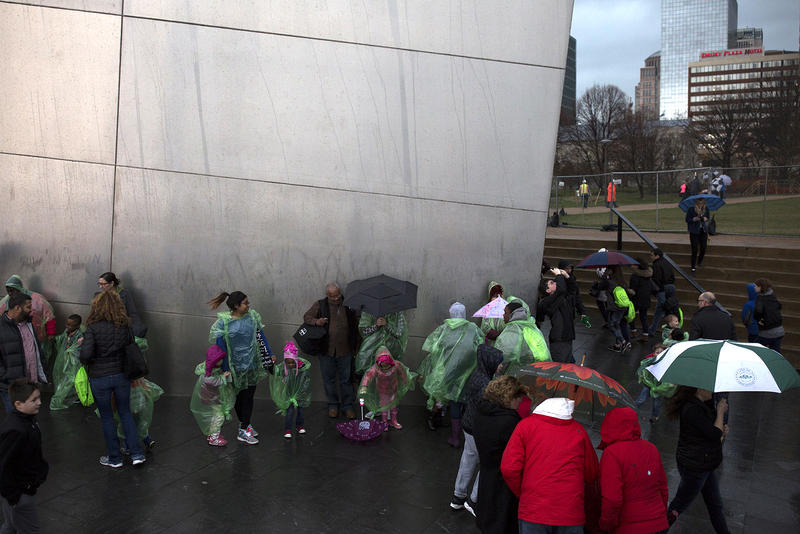 Visitors stand along one side of the Gateway Arch to hide from wind and rain after walking across the Park Over the Highway.