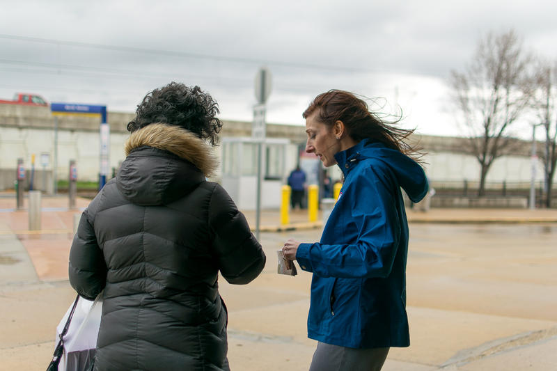 Jessica Mefford-Miller of Metro Transit (right) hands a rider a pamphlet on Metro's suggested service plans at an informational meetin. April 3, 2018.