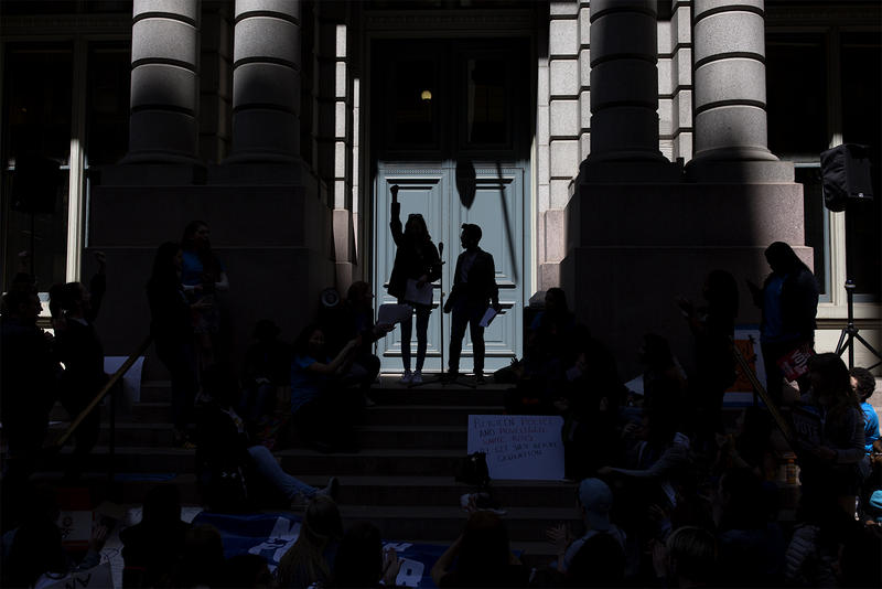 Students gives speeches as a crowd stands outside the Old Post Office on Olive Street.