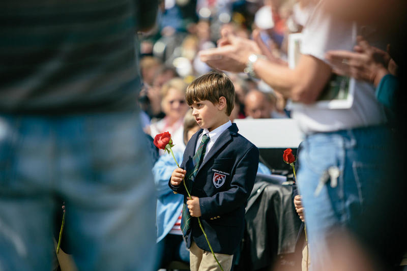 A boy carries a rose at a Vietnam Memorial Ceremony at the College of the Ozarks, near Branson.