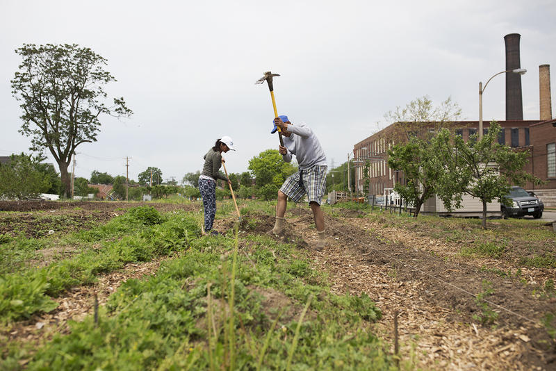 Suk (right) and Chandra Sapkota prepare gardens beds for planting at Global Farms' south St. Louis location on a Saturday in May 11, 2018.
