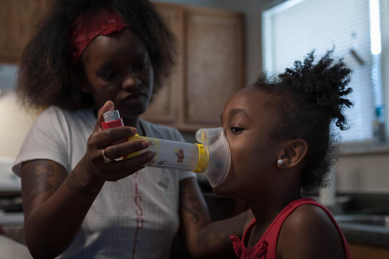 Cenya Davis puffs on her inhaler earlier this month. The 8-year-old student at Gateway Elementary School in St. Louis has been to the hospital three times for breathing trouble starting in December. She now regularly uses the inhaler.