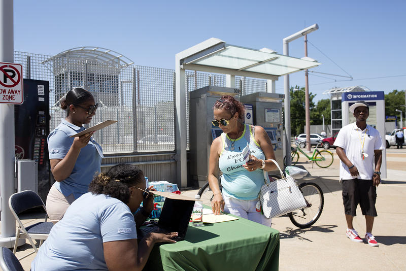 Stephanie Schuermann, center, sets up a future appointment at the People's Health Centers mobile clinic at the Forest Park-Debaliviere metro stop.  June 5, 2018