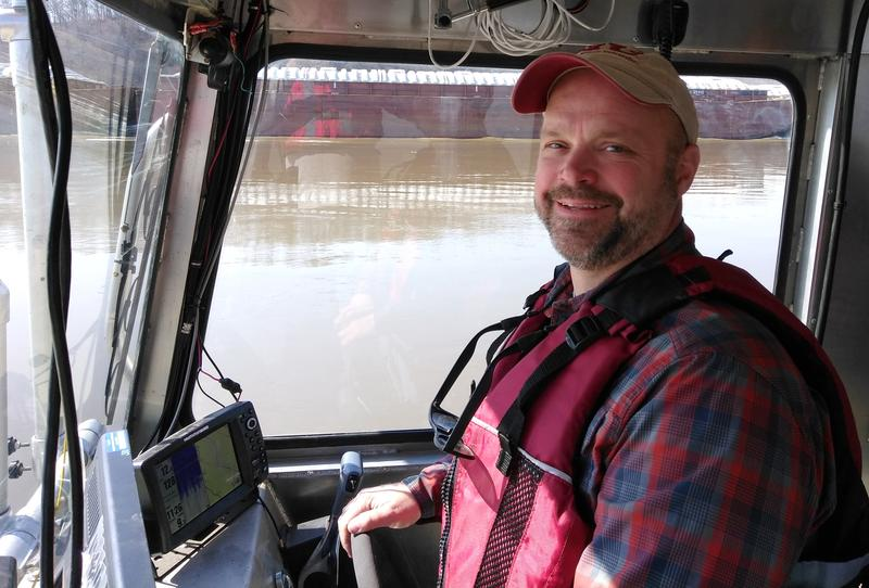 "SIUC faculty member Jonathan Remo, who was part of Monday's ""St. Louis on the Air"" discussion of water policy, passes a barge while captaining a research vessel near Grand Tower, Illinois."