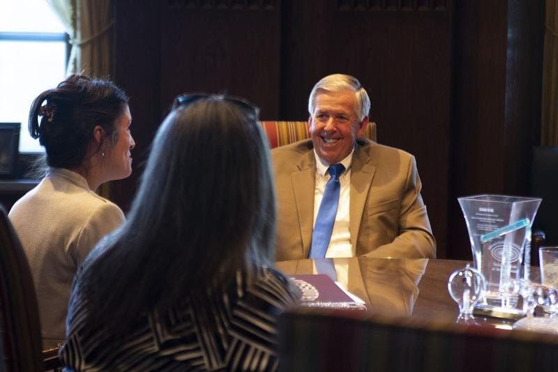 Gov. Mike Parson talking with Jefferson City Mayor Carrie Tergin, at far left.