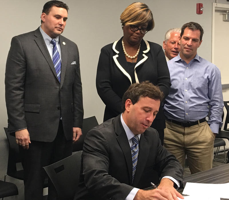 St. Louis County Executive Steve Stenger signs an executive order that bans county officials from reviewing an applicants criminal history during the initial application process. June 11, 2018.