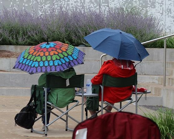 Two fans take cover from the rain to watch the Cardinals vs. Brewers at Who's on Deck? What's on Draft?