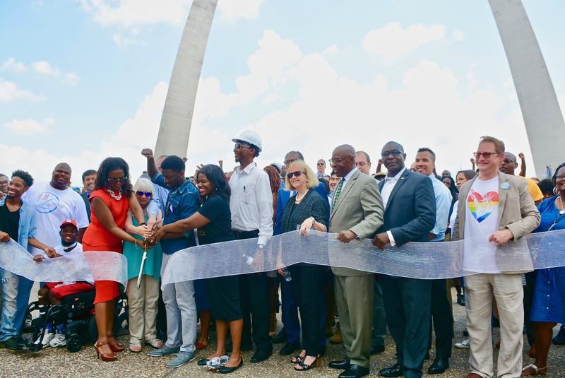 "Attendees at Friday's ""People's Ribbon Cutting"" celebrate near the Gateway Arch grounds in St. Louis."