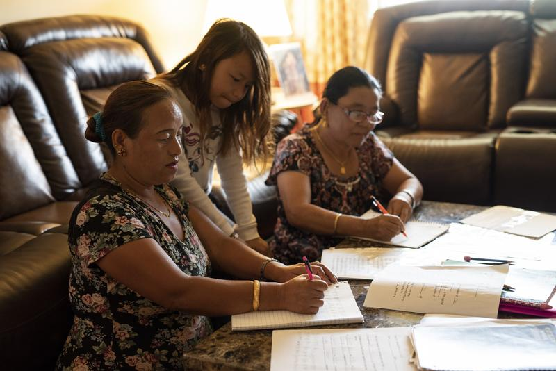 Ganga Mongar, left, and Sancha Subba, right, receive help from Mongar's daughter Anjali while practicing for the writing portion of the naturalization test. Both women have learned how to read and write to prepare for the test.