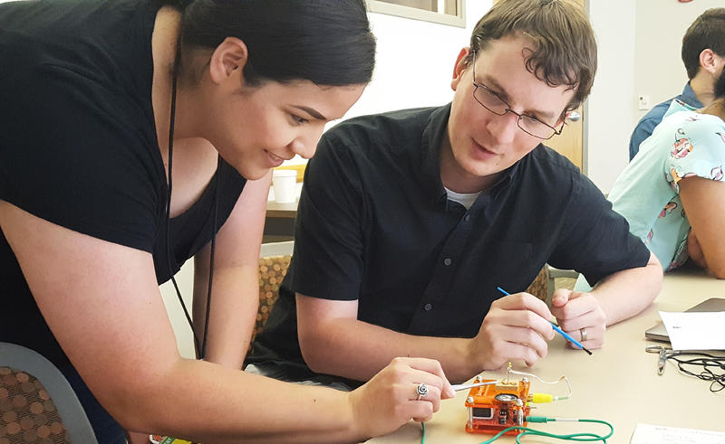 Natalia Cantu stimulates the neurons in a cockroach leg at a lab session on July 25, 2018, while fellow program participant Ryan Evans observes.