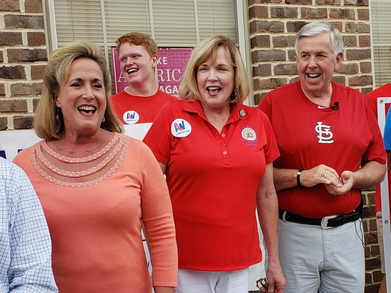 Missouri Gov. Mike Parson, right, laughs along with U.S. Rep. Ann Wagner, in orange, during a Republican rally on Saturday, July 28, 2018,  in south St. Louis County.