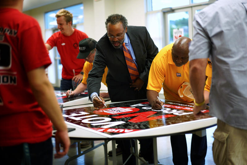 Missouri NAACP President Nimrod Chapel signs a poster urging voters to repeal right to work on August 7, 2018.