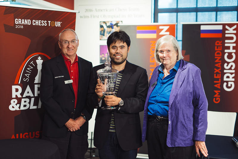 Hikaru Nakamura won the second Annual Rapid & Blitz tournament which took place Aug. 10-16, 2018. Nakamura, center, displays his trophy alongside St. Louis Chess Club founders, Rex and Jeanne Sinquefield.